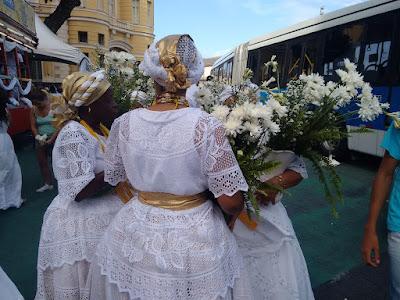 Fotografia colorida de três mulheres de vestidos longos rodados brancos usando turbantes brancos com detalhes em dourado. Elas seguram vasos brancos com flores do campo brancas.