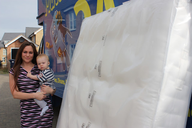 Lady holding baby stands next to Mattressman truck, with new mattress