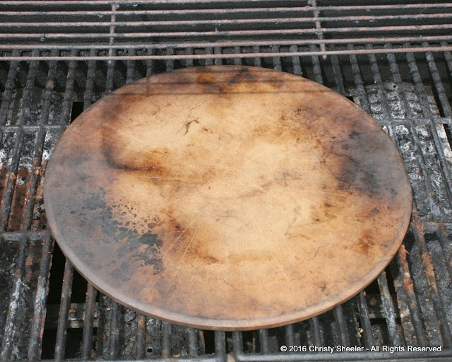 Pizza stone resting on grill to begin preheating process.  Making pizza on the grill with a pizza stone.