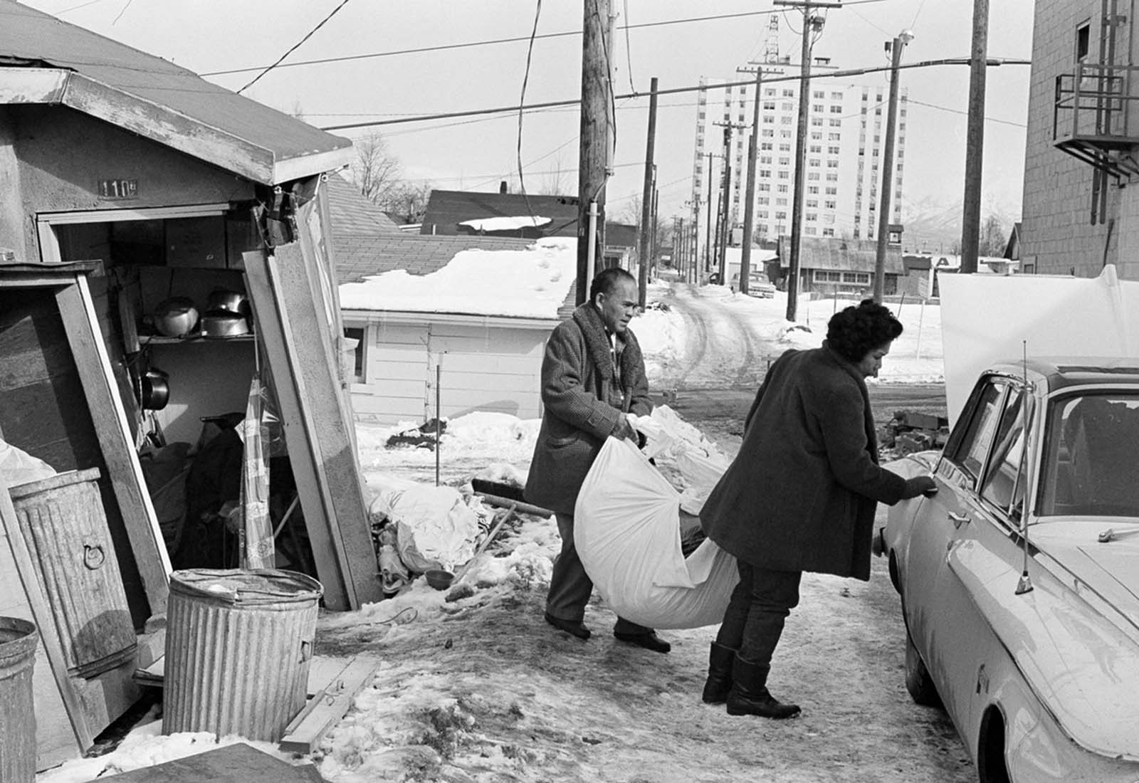A man and his wife carry a load of possessions from their earthquake-shattered home in Anchorage, Alaska, on March 31, 1964.