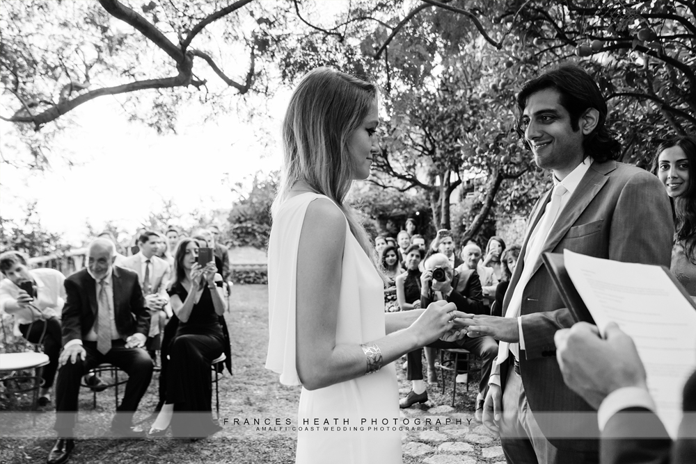 Bride and groom exchanging rings during garden wedding ceremony