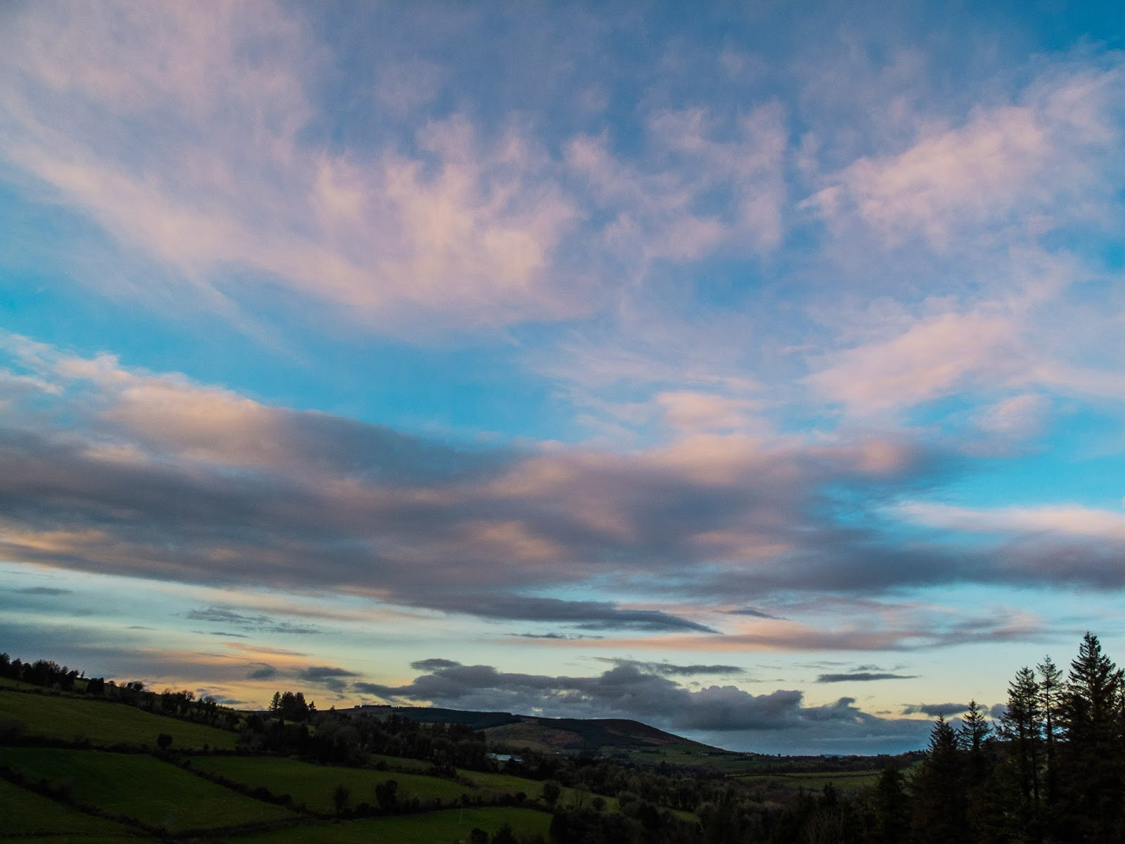 Rolling green hills of Ireland with colourful clouds at sunset.