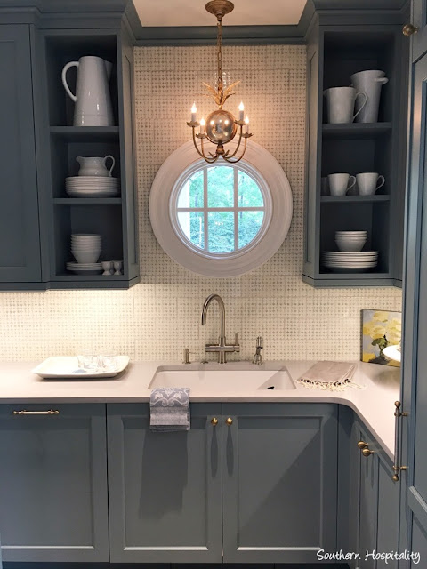 Blue cabinets, beautiful tile backsplash, round window and brass hardware in butler pantry