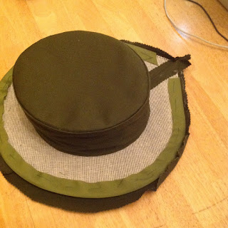 Image is of a hat about half-finished. The top part is covered in dark green fabric, but the brim has a layer of white buckram and light green fabric exposed.