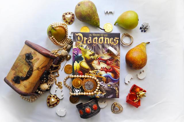 Peras, joyas, y monedas de chocolate rodean la caja del juego