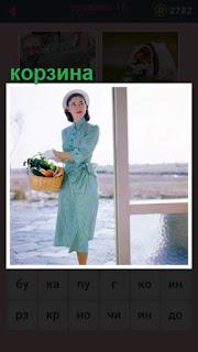 стоит женщина с корзиной, в которой лежат разные овощи