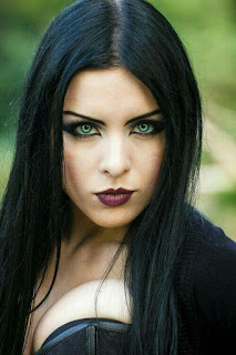 Mujer con ropa estilo gótico, con grandes ojos verdes, labios pintados de negro y pelo largo negro. Viste un corsét y chaqueta negras.