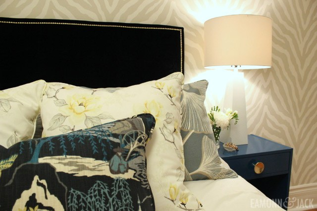 pillows an a bed beside a blue side table
