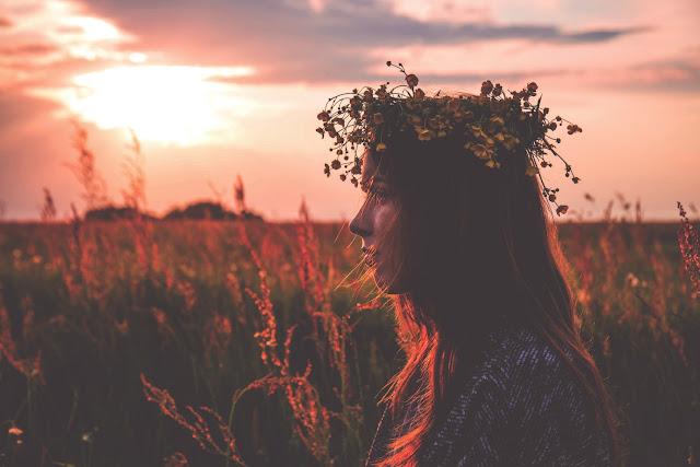 Mladá žena na louce při západu slunce s věncem na hlavě