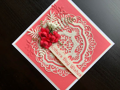 Hand made Mothers Day card with die cut doily background, flowers and leaves cluster and stamped greeting