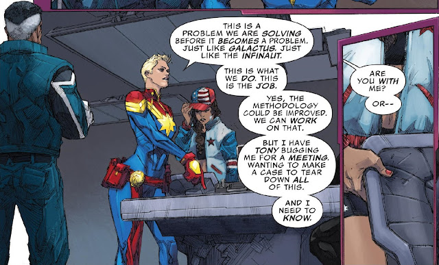 Captain Marvel standing imposingly in front of a table with the empty briefcase on it addressing the team.