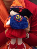 Kwokkie Doll from behind where she can show off her royal blue cape with yellow initials inside a red border.  Her harmony day clothes consist of an orangge beanie, red dress and red sneakers with white laces.  She is wearing a red yarn ribbon in her black hair and an orange sleeveless vest for Harmony Day.