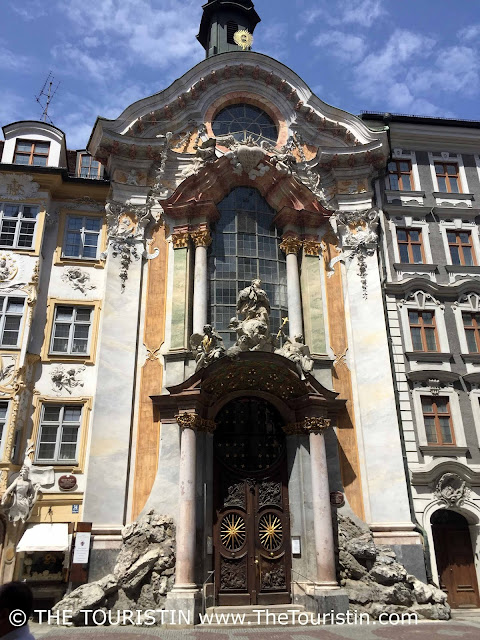 Giant entrance door and front of a church on a pedestrian street.
