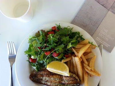 Plate of grilled fish, salad and chips.