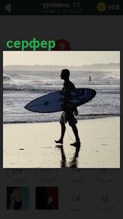Парень серфер с доской идет по берегу с желанием поймать волну