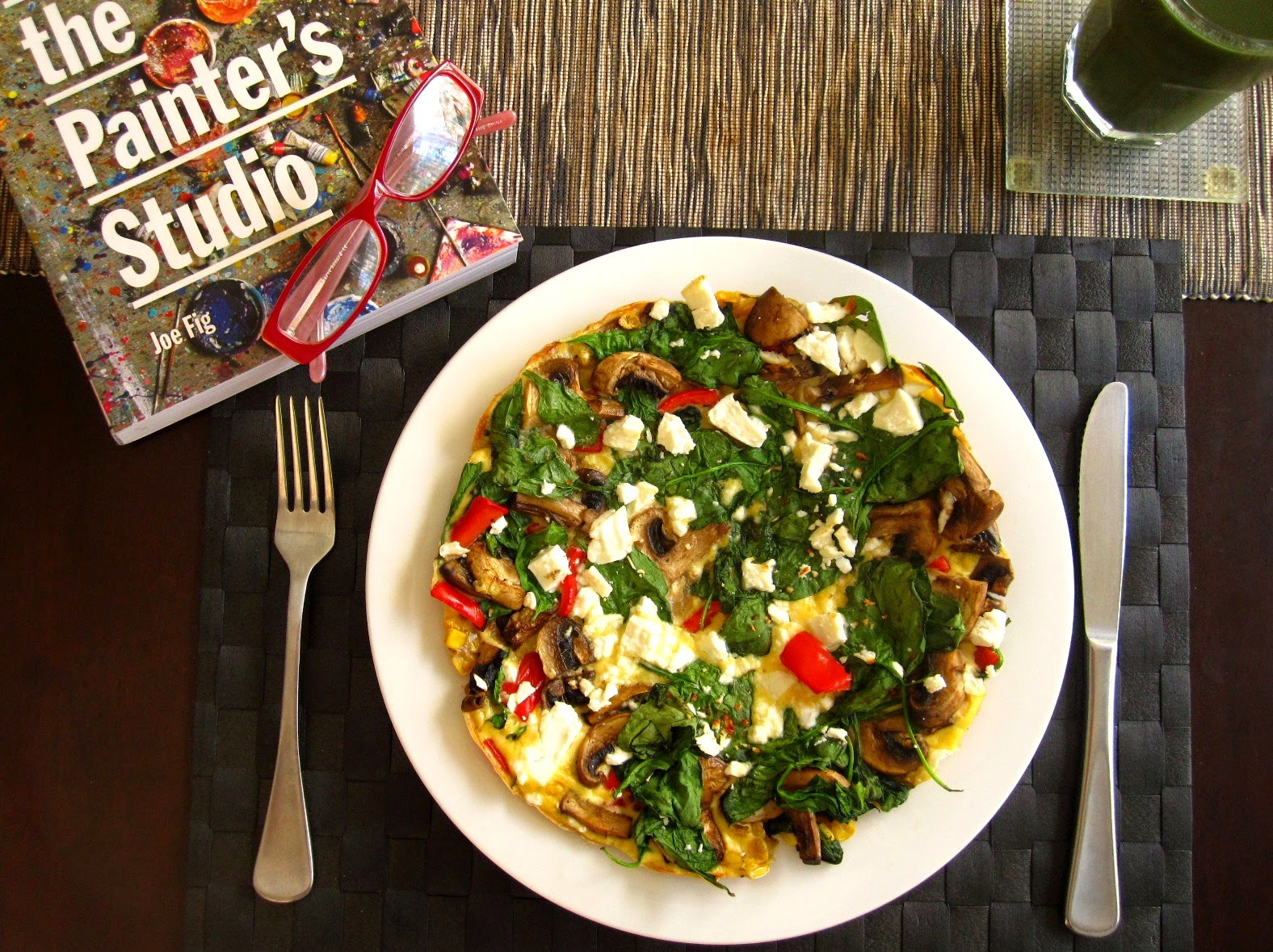 Aerial view of a dining table showing a vegetable frittata, a spiralina juice and a copy of the book 'Inside the Painter's Studio' with a pair of reading glasses on top of it.