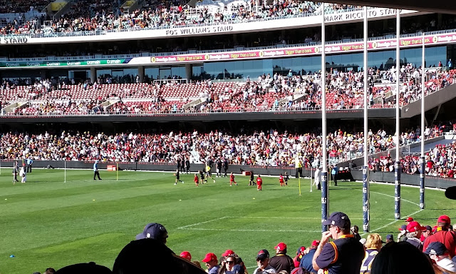 An Auskick game in progress on the oval. The players are in teams: red vs black.  The large goalposts are on the right hand side.  On the oval are mini goal posts marking the boundaries of the mini-matches.  In the background is a three-tiered stand with glass viewing boxes at the back of the middle tier.
