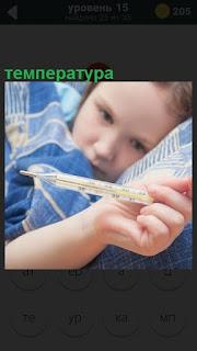 Ребенок показывает градусник с температурой, лежа в постели на подушке