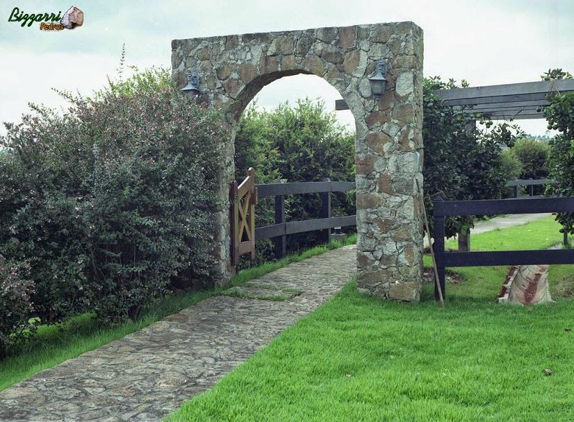 Caminho com pedra rústica tendo no início do pórtico de pedra e a execução do paisagismo