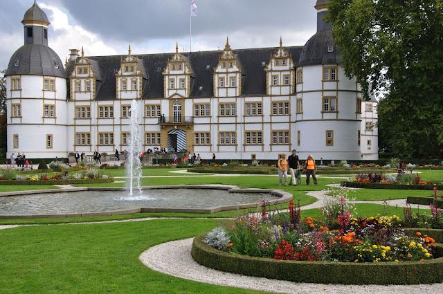 Das Weiße Schloss Neuhaus mit seinen Ockerfarben abgesetzten Fenstern und dem schwarzen Schieferdach. Im Vordergrund Blumenbeete und ein Springbrunnen.
