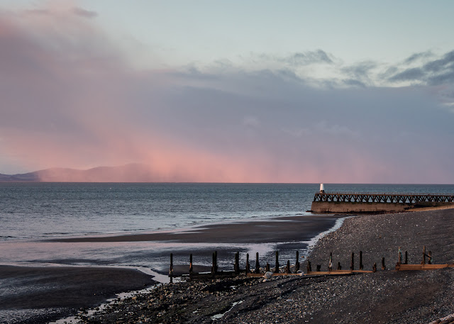 PHoto of Maryport pier at sunset with snow approaching from across the Solway Firth