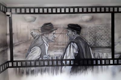 """Obraz wykonany na ścianie w czarno-bieli, artystyczne malowanie ściany we wzór z filmu """"Sami Swoi"""" czarno-biały mural"""