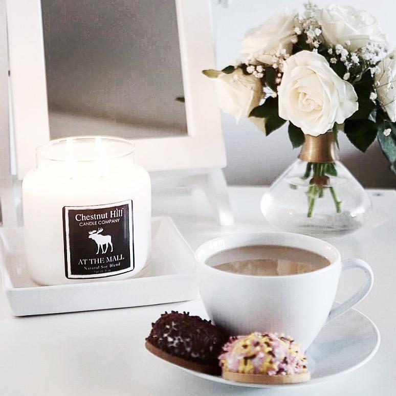 filiżanka kawy z mlekiem, ciasteczka, świeca zapachowa i białe kwiaty w wazonie