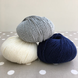 Three balls of Drops Cotton Merino yarn in blue, white and grey