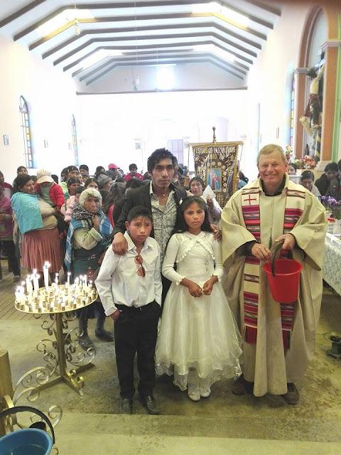 Padre Claus mit zwei Täuflingen und ihrem Paten. Der Pate ist ihr Lehrer.