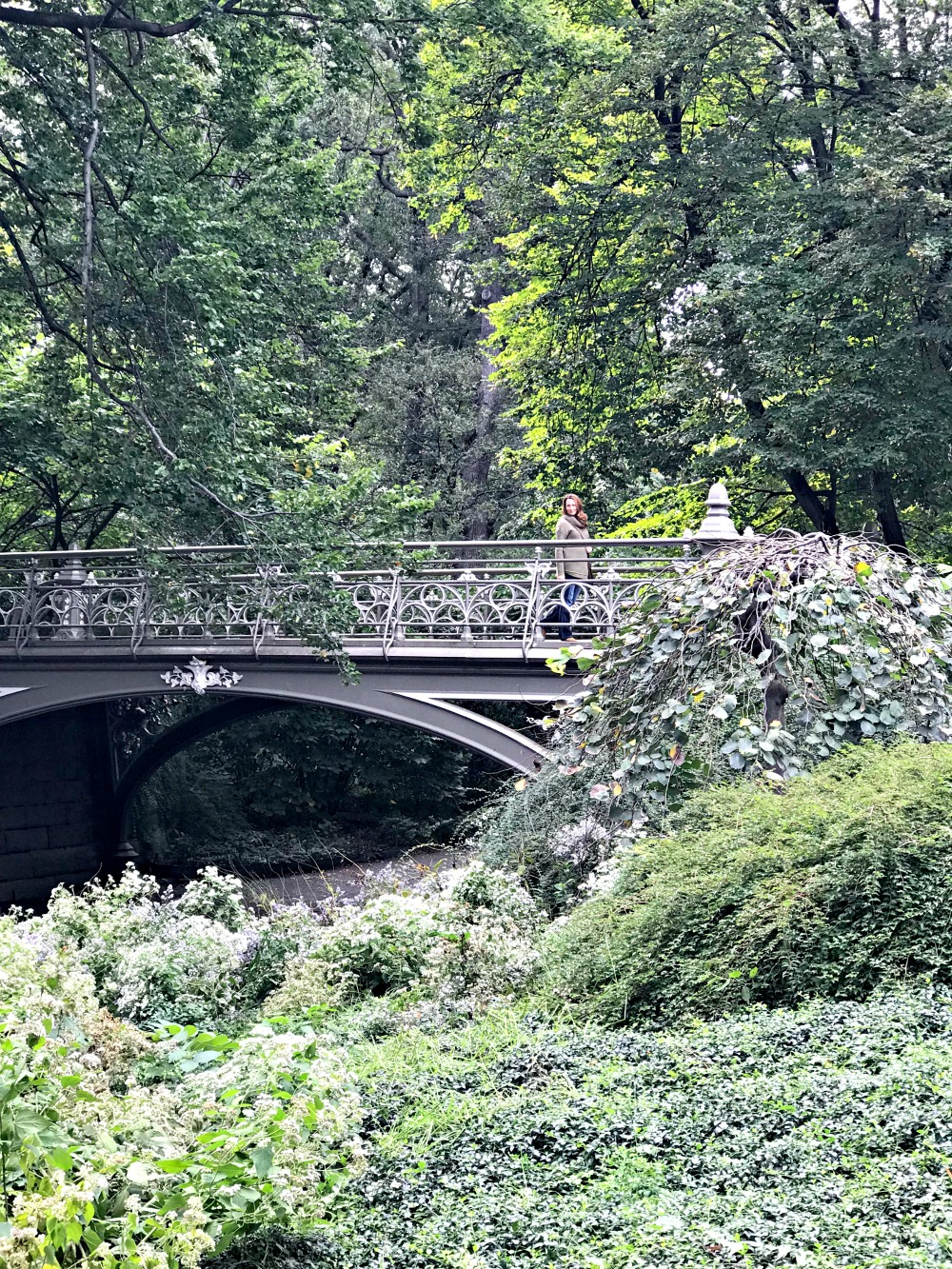 woman strolling over a bridge in Central Park