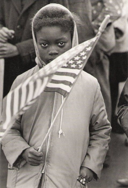 Photo of a solemn looking young Black girl holding an American flag at a Civil Rights Protest March, North Carolina 1961 by photographer Declan Haun