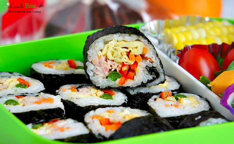 Delicious Lunch Box: Kimbap with omelet, cooked ham, asparagus, peppers and carrots.