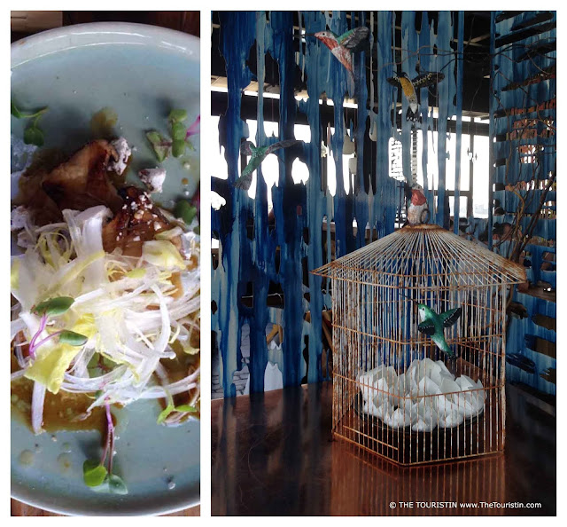 Lavishly decorated food on a light green plate. A bird cage and bird decoration in the entrance of a restaurant.
