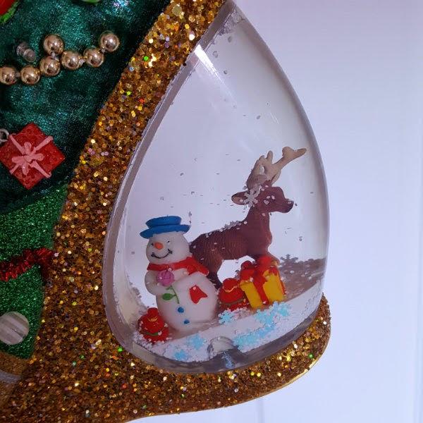 close up of glitter platform shoe showing snowman and reindeer inside snowglobe heel
