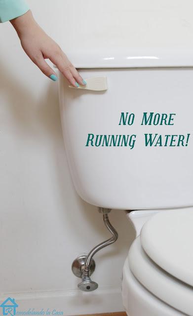 white toilet tank with hand ready to flush it.
