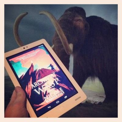 A pale hand holds a white Kobo with Archivist Wasp's red and green cover on its screen. The cover features a long-haired person in silhouette at the top of a twisting path that leads towards some jagged red mountains. Behind the Kobo is a taxidermied woolly mammoth in a faux-arctic environment. It has impressive tusks.