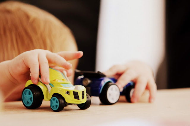 Photo of toddler playing with cars