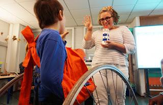 Dra. Inês interage com um aluno fazendo o movimento com a mão do piscar da luz de um farol
