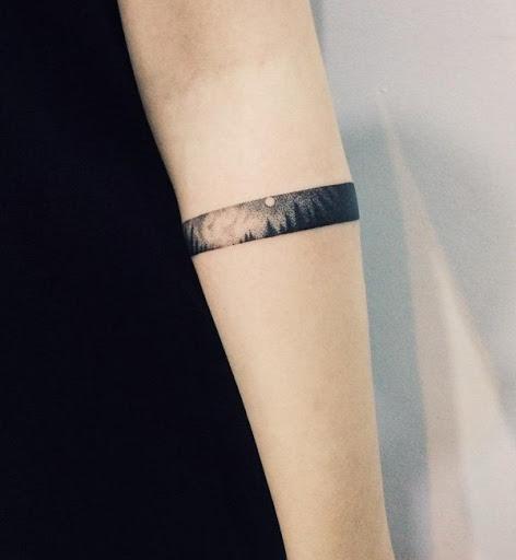 As meninas também poderia ir com a floresta tatuagens e aqui está uma encantadora e única maneira de fazê-lo. É uma pequena paisagem de uma floresta à noite, concebido como uma braçadeira.