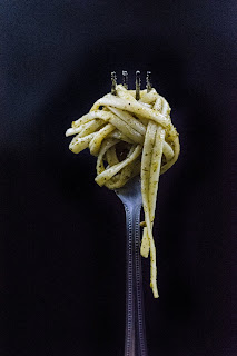 Photo of a fork with garlic scape pesto pasta twisted around the tines. https://trimazing.com/