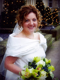 Bride with curly hair in wedding dress holding a bouquet