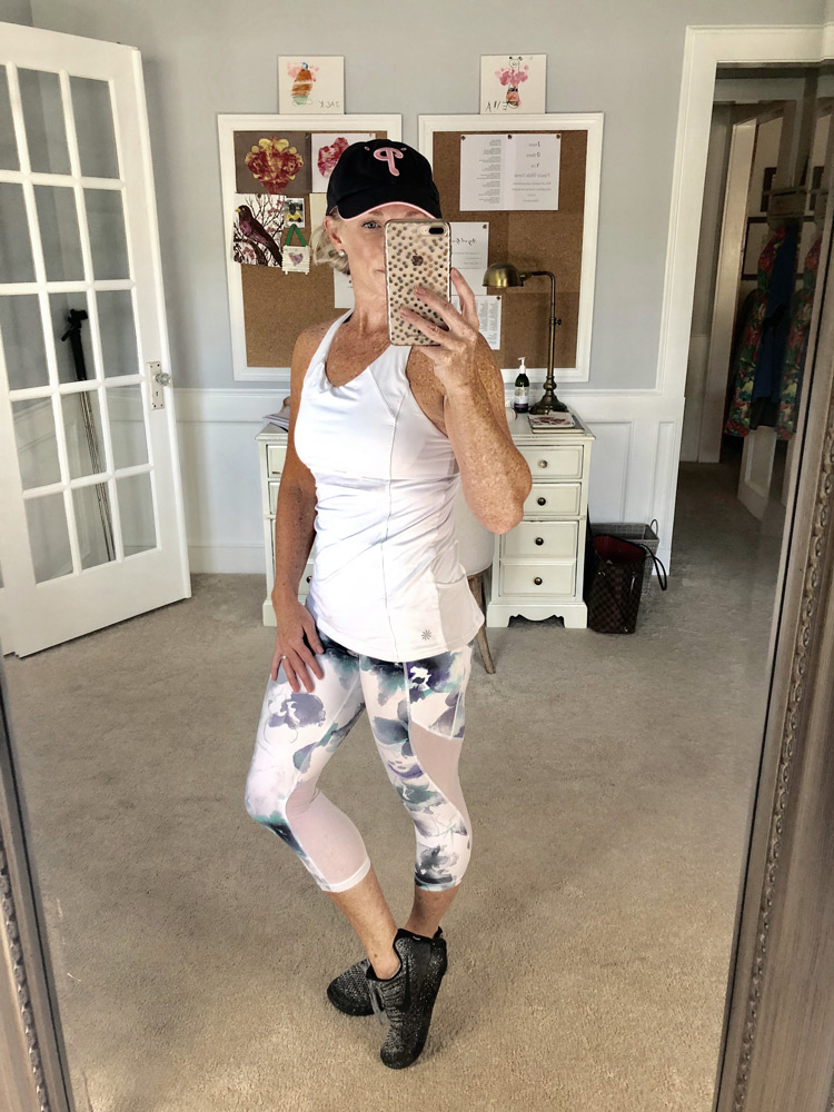 white athletic tank top with floral athletic leggings and nike sneakers