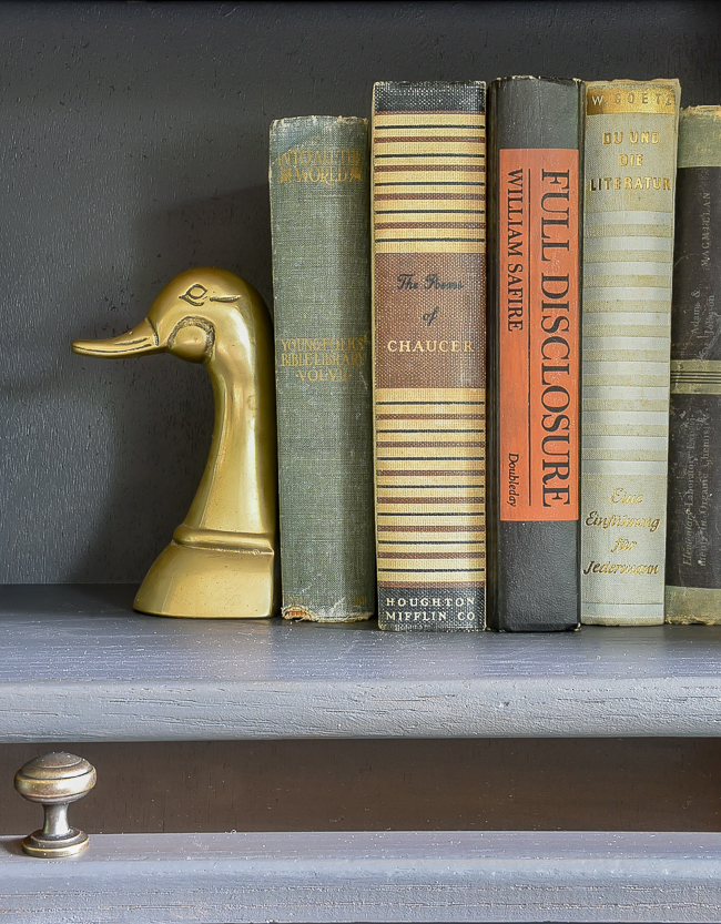 Brass duck bookends and vintage books styled in a barrister bookcase
