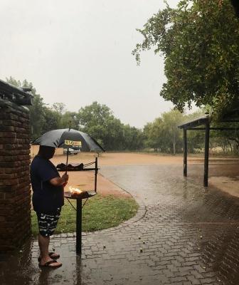 Barbeque with umbrella in the rain