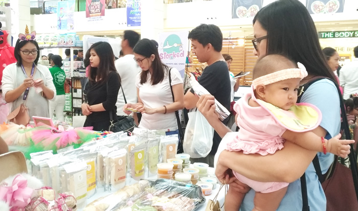 Mommy and baby checking out organic baby products at Gaia stuff stall