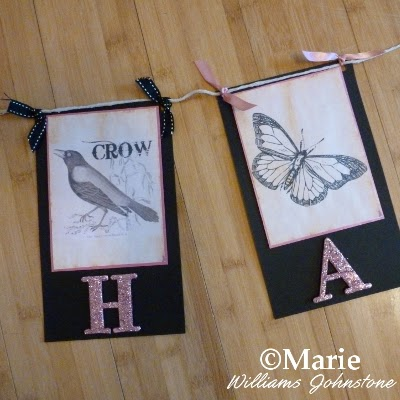 Section of a paper banner bunting with crow and butterfly designs and ribbon decoration