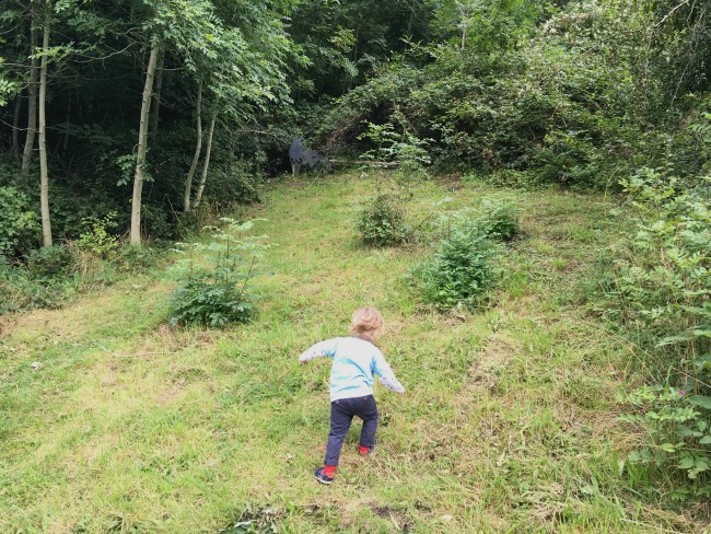 toddler-climbing-very-steep-slope-with-a-metal-wolf-jus-visible-in-greenery