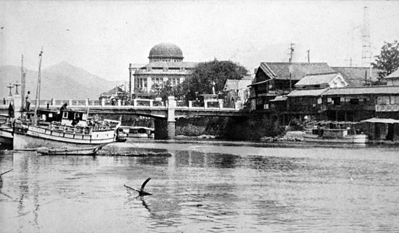 Looking upstream on the Motoyasugawa, toward the Product Exhibition Hall building (dome) in Hiroshima, before the bombing. The domed building was almost directly below the detonation, which occurred in mid-air, about 2,000 feet (600 meters) above this spot. Today, much of the building remains standing, and is known as the Atomic Bomb Dome, or the Hiroshima Peace Memorial.
