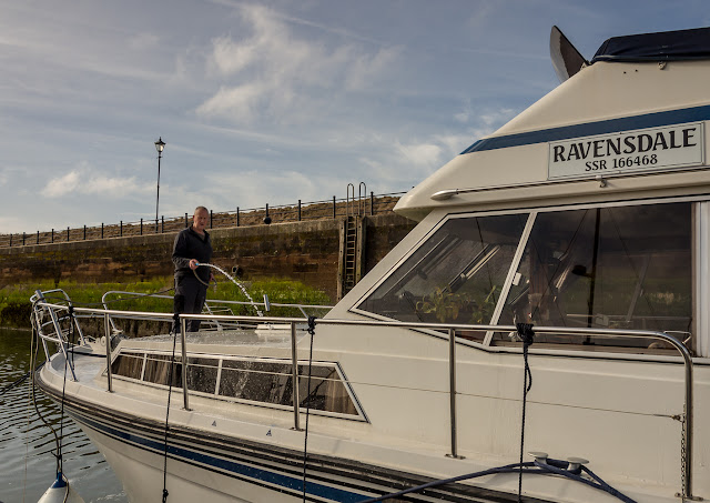 Photo of Phil washing off the boat wash on Ravensdale's foredeck