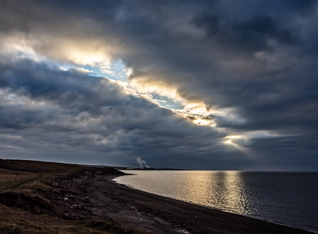 Photo of light breaking through the clouds in a stormy sky over the Solway Firth
